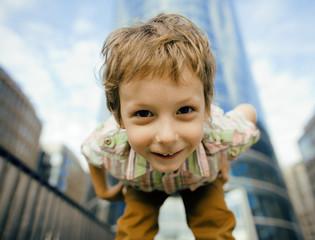 little cute boy standing near business building, smiling