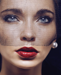 beauty brunette woman under black veil with red manicure close