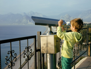 little cute boy looking through telescope at sea viewpoint in