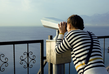 young woman looking through telescope at sea viewpoint in