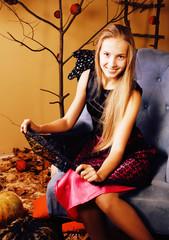 blond cute girl in halloween interior with pumpkin, cute teen