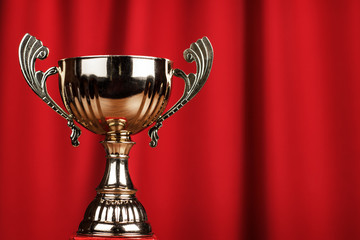 golden trophy cup over red background