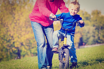 father teaches son to ride bicycle