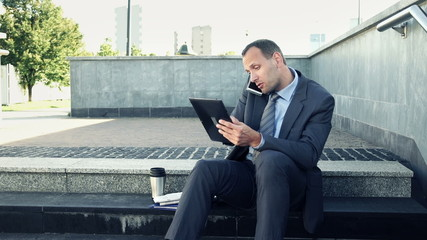 Angry businessman with tablet computer talking on cellphone in t