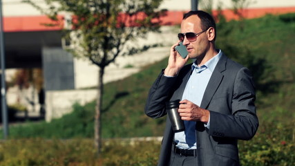 Businessman talking on cellphone and drinking coffee in the city