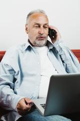 Rentner spricht am Telefon, laptop in Lappe