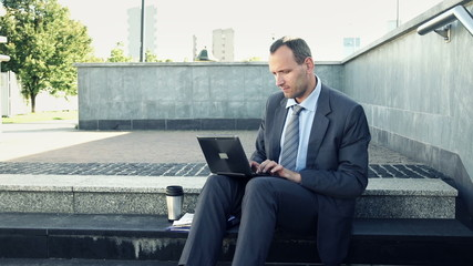Businessman hands typing on laptop in the city