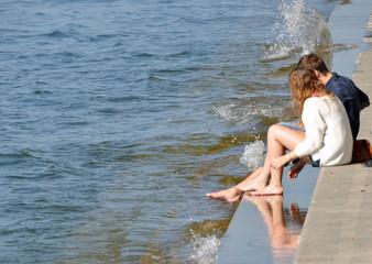 Füße im Wasser an der Promenade