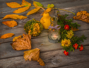 Burning lamp, pumpkins and leaves on a wooden table