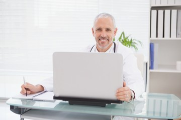 Smiling doctor using laptop and writing