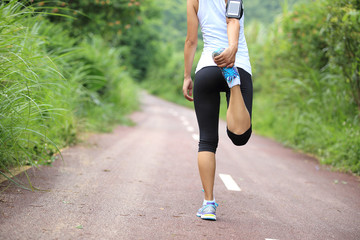 woman runner warm up on forest trail