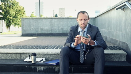 Businessman listening to music on smartphone while sitting on st