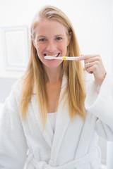 Happy blonde brushing her teeth