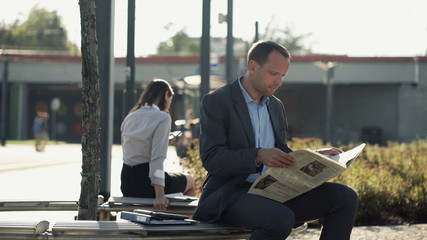 Young businessman reading newspaper on bench in the city