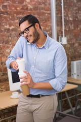 Businessman with mobile phone and coffee in office
