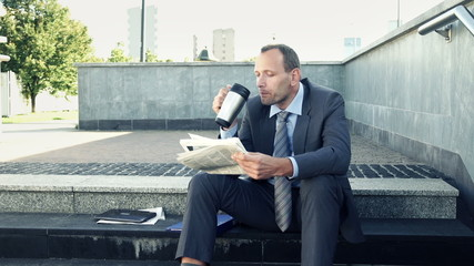 Businessman reading newspaper and drinking coffee while sitting