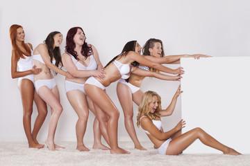 Happy girls in underwear pulling whiteboard