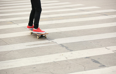 woman legs skateboarding at city
