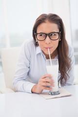 Pretty businesswoman drinking milk at her desk