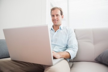Casual man using laptop on the couch