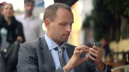 Businessman texting, sending sms on smartphone in cafe