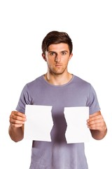 Young man holding ripped paper