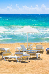 Parasols and sun loungers on the beach. Ionian Sea