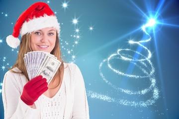 Composite image of festive blonde showing fan of dollars