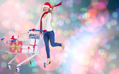 Composite image of festive blonde pushing trolley full of gifts