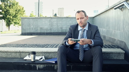 Businessman texting, sending sms on smartphone in the city