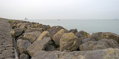 Trawler fishing on a lake along a dike