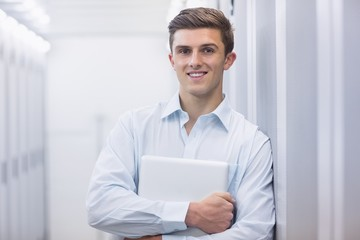 Portrait of a smiling technician holding a laptop