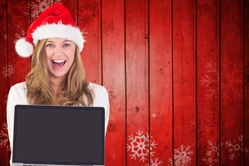 Composite image of festive blonde showing a laptop
