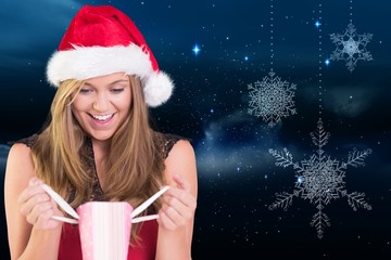 Composite image of festive blonde opening a gift bag