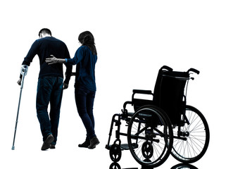 injured man  with crutches   with woman  walking away from  whee