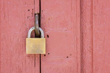 closeup of lock on the middle of pale red wood door