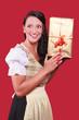 canvas print picture - Junge Frau mit Dirndl und grossem Geschenk in der Hand