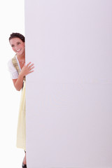 Junge Frau im Dirndl versteckt sich hinter einer Wand