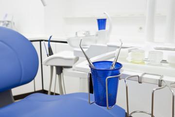 Pinzetten in einem blauen Plastikbecher in einer Zahnarztpraxis.