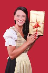 Junge Frau mit Dirndl und grossem Geschenk in der Hand