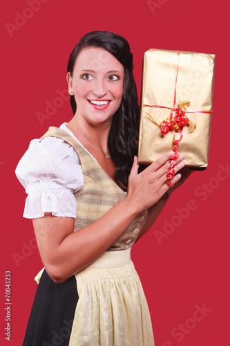 canvas print picture Junge Frau mit Dirndl und grossem Geschenk in der Hand