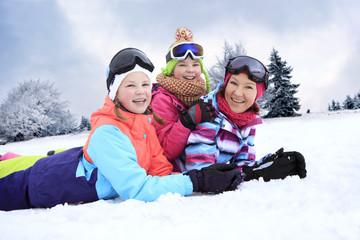 Mutter und Töchter liegen im Schnee, lächelnd, glücklich