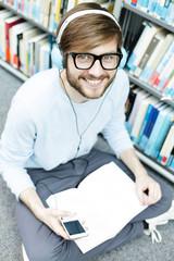 Student in einer Universitätsbibliothek sitzt auf dem Boden