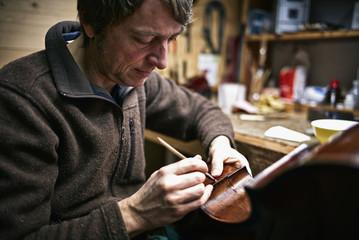 Geigenbauer in seiner Werkstatt