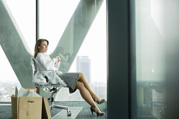 Geschäftsfrau auf leerer Büroetage mit Karton, Blick aus Fenster