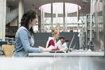 Studenten mit Laptops in einer Universitätsbibliothek