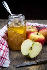 Glas selbstgemachte Apfel-Marmelade, Geschirrtuch und Äpfel auf Holztisch