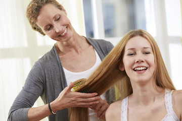 Mutter bürstet die Haare ihrer Tochter