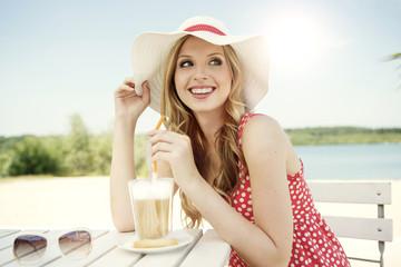 Lächelnde junge Frau mit Latte Macchiato