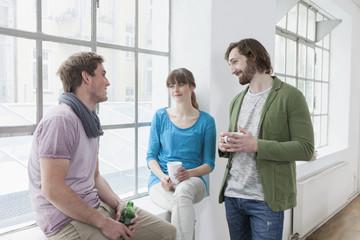 Drei Kollegen kommunizieren in einem kreativen Büro